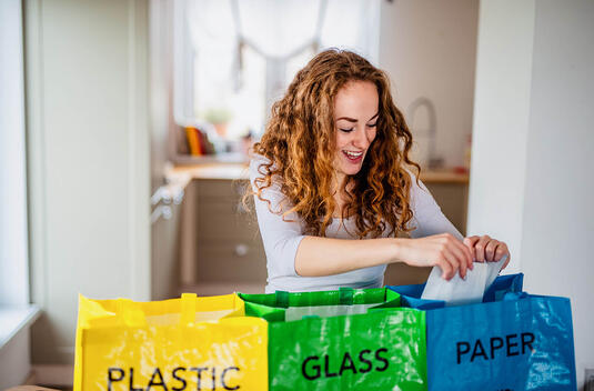 Woman Recycle Separating Glass Paper Plastic